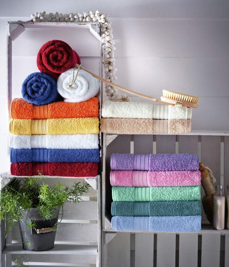 caisses réutilisées dans des étagères murales pour ranger des serviettes, une plante et d'autres articles de salle de bain dont vous pourriez avoir besoin