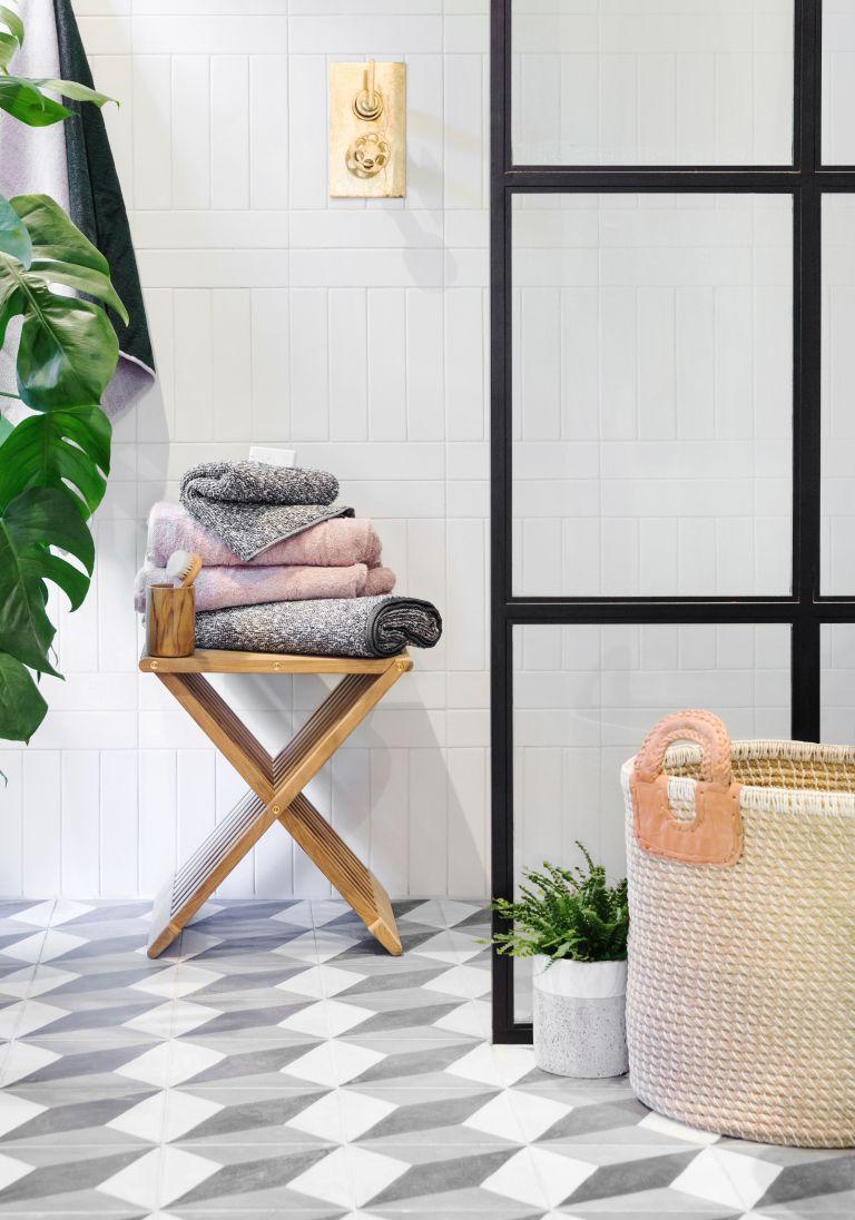 un petit tabouret en bois est une belle unité de rangement, vous pouvez également vous asseoir dessus, alors procurez-vous un pliant pour votre salle de bain