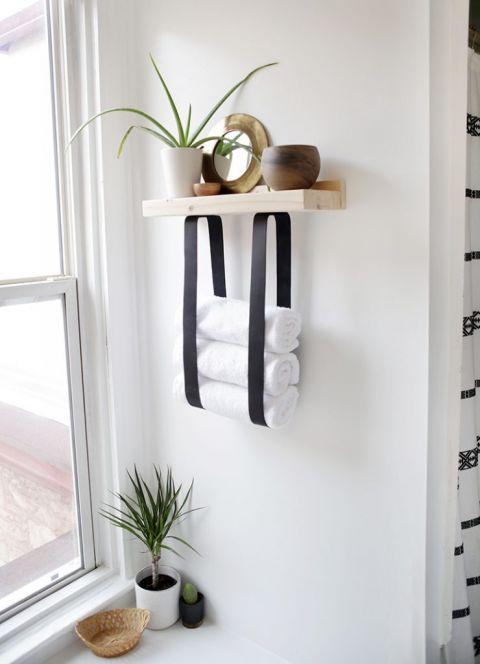 une étagère à serviettes en bois et en cuir vous permettra de ranger non seulement les serviettes mais aussi la décoration et les accessoires