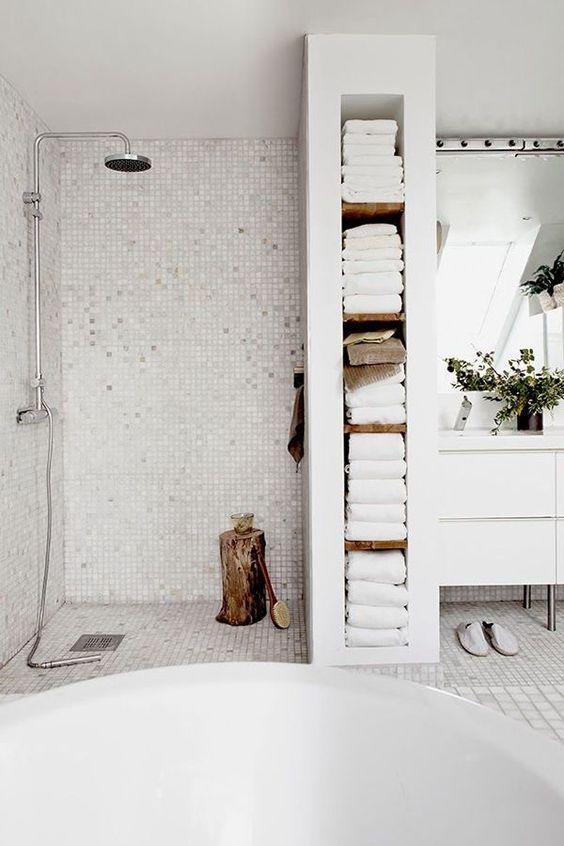 une étagère intégrée qui sert également de séparateur d'espace de douche et contient toutes les serviettes est une solution intelligente