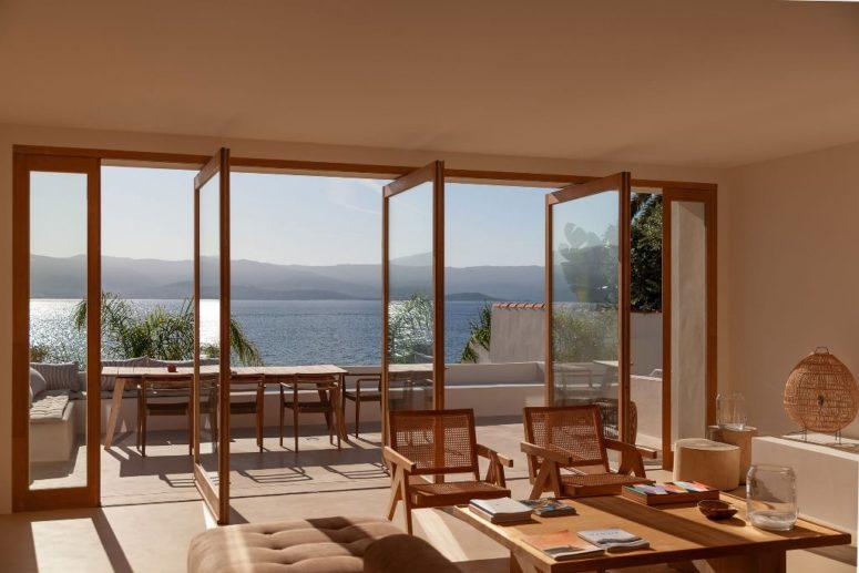 Plusieurs portes vitrées pivotantes ouvrent l'espace intérieur sur une terrasse avec un espace salle à manger