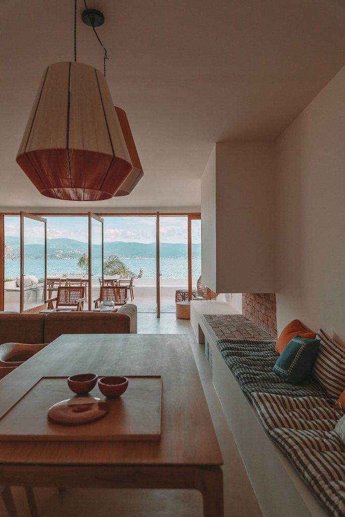 Le salon avec des suspensions, une cheminée à foyer ouvert, des meubles chics et il est entièrement ouvert sur l'extérieur