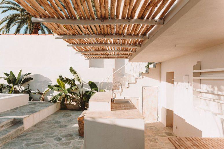 Il y a une cuisine extérieure faite dans des tons neutres et avec un toit naturel