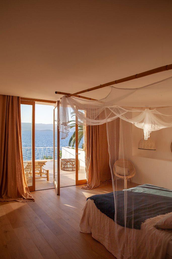 La chambre principale offre une vue imprenable sur la mer et un grand balcon avec chaises longues, un lit à baldaquin