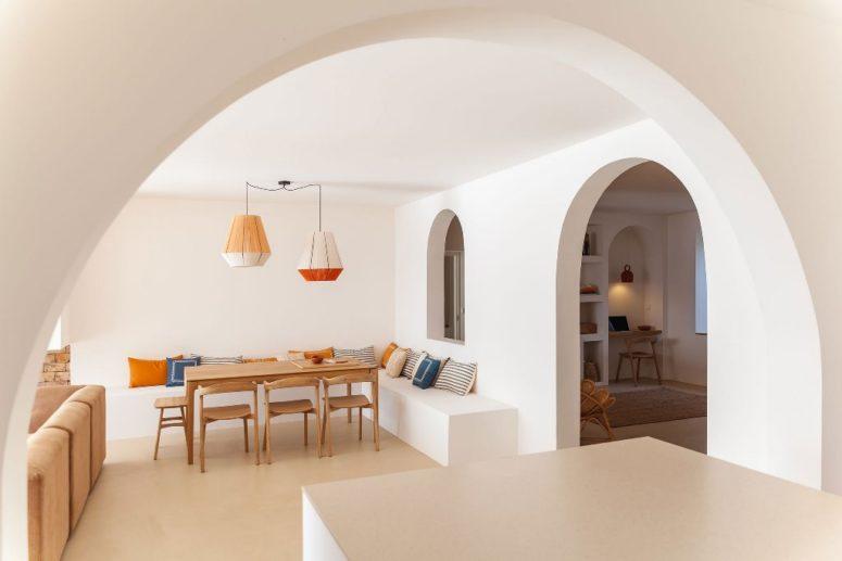 L'espace salle à manger intérieur comprend un banc d'angle, des oreillers colorés et des chaises en bois