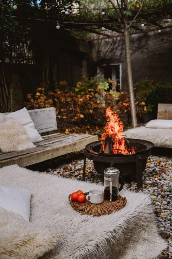 une cour d'automne avec des bancs en bois, de la fausse fourrure, un foyer et des oreillers est super accueillant