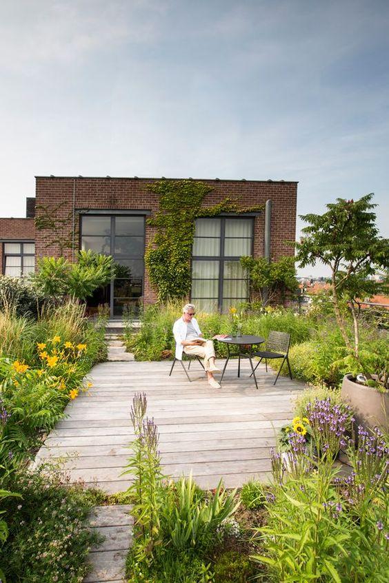 une petite cour accueillante avec beaucoup de verdure et de fleurs lumineuses, avec une terrasse en bois et des meubles simples