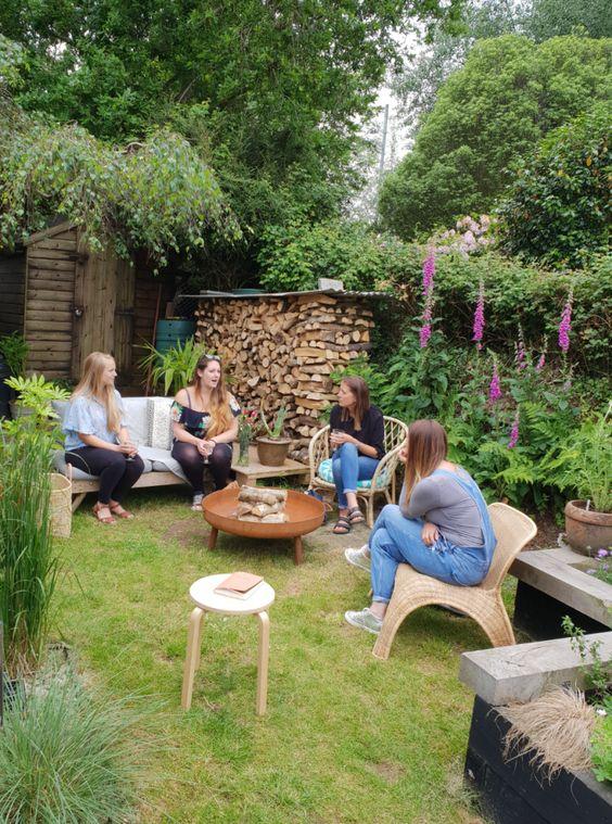 une cour rustique avec une pelouse verte avec des meubles en bois et en rotin, avec beaucoup de verdure et de fleurs lumineuses