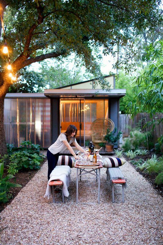 une cour arrière moderne avec de la verdure et des arbres, des bancs en bois et en métal et une table à manger ainsi que des oreillers à rayures