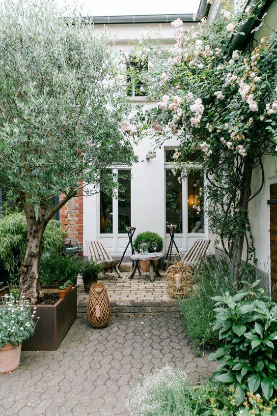 une cour moderne simple avec des meubles en bois, des bougies dans de grandes lanternes à bougie et des arbres et des fleurs