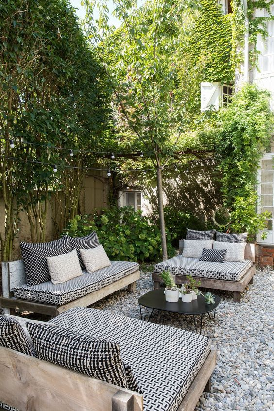 une cour arrière monochromatique avec des meubles en noir et blanc et beaucoup de verdure autour
