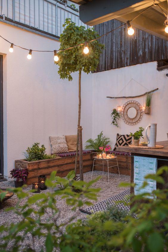 une petite cour boho avec du gravier au sol, un banc d'angle en bois, de la verdure, des lumières, des oreillers boho et des lumières