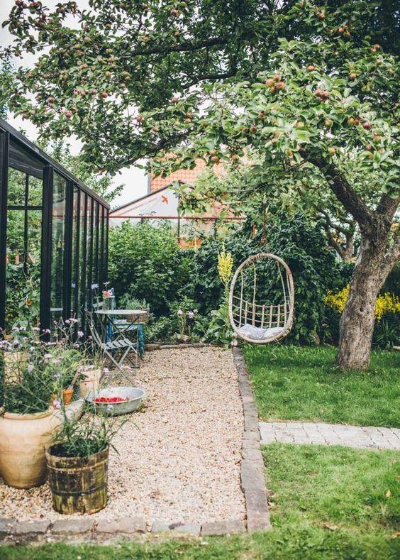 une petite cour avec une chaise suspendue, des meubles de jardin, des fleurs en pot et une pelouse verte