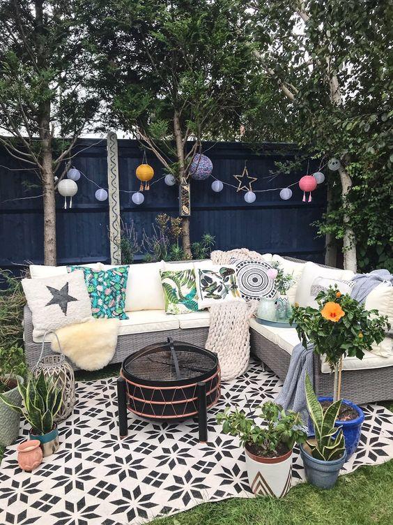 une petite cour avec une pelouse verte, des lampes en papier, un canapé en osier avec des oreillers imprimés et des plantes en pot