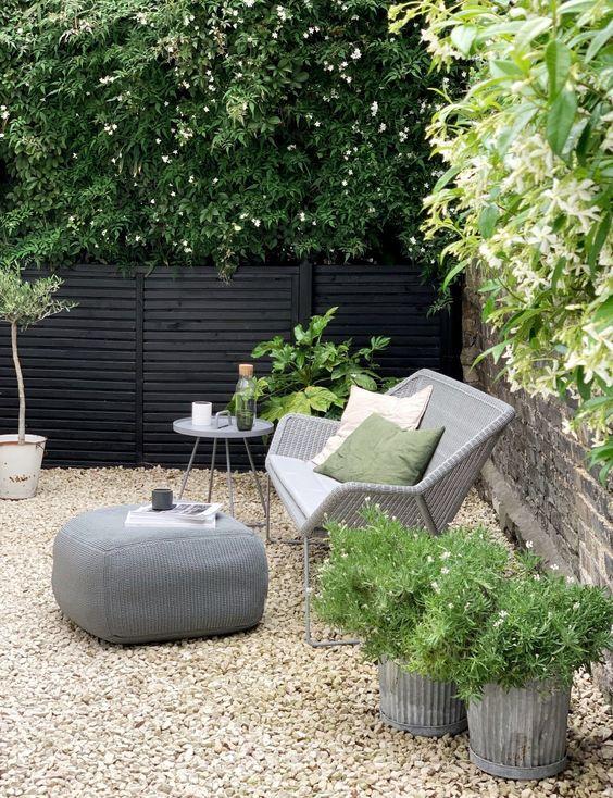 une petite cour moderne avec du gravier au sol, avec des meubles en rotin et des plantes en pot et des fleurs