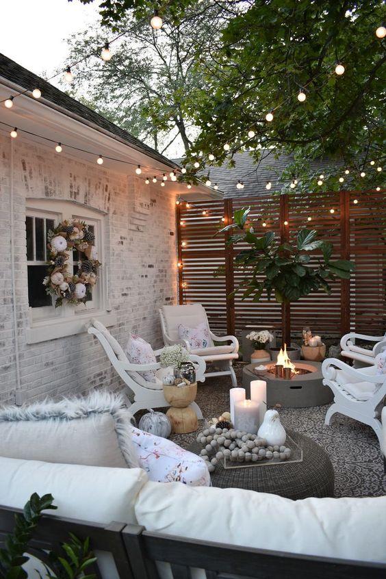 une petite cour éclectique avec un foyer, des meubles vintage blancs et des lumières partout