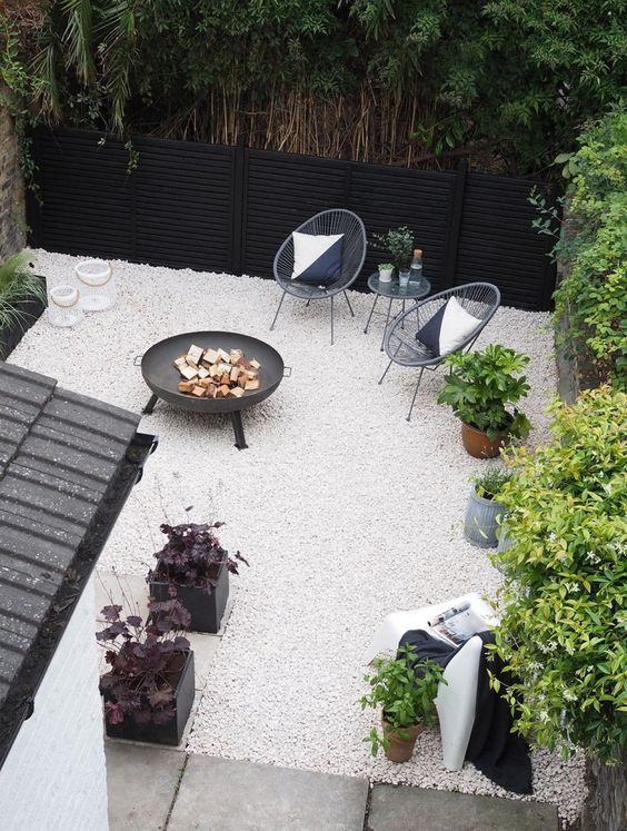 une petite cour moderne avec du gravier blanc, des chaises en rotin, un foyer et des plantes en pot est super élégante