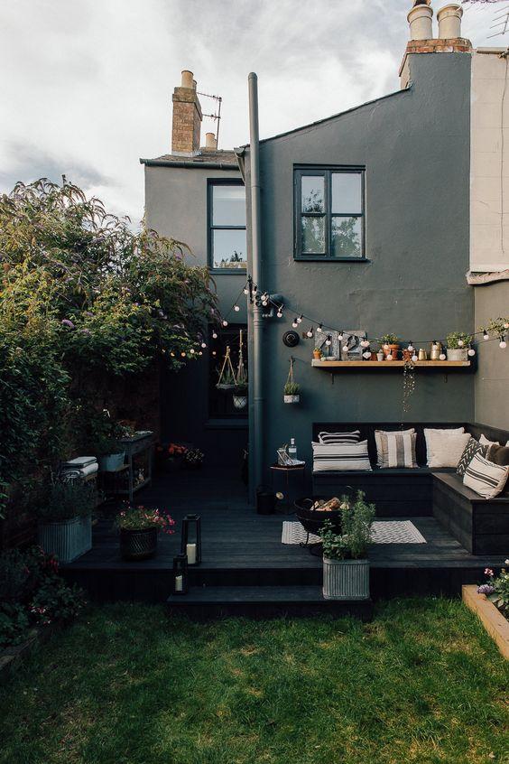 une petite cour scandinave avec une terrasse noire, un banc d'angle noir, une pelouse verte et quelques fleurs tout autour