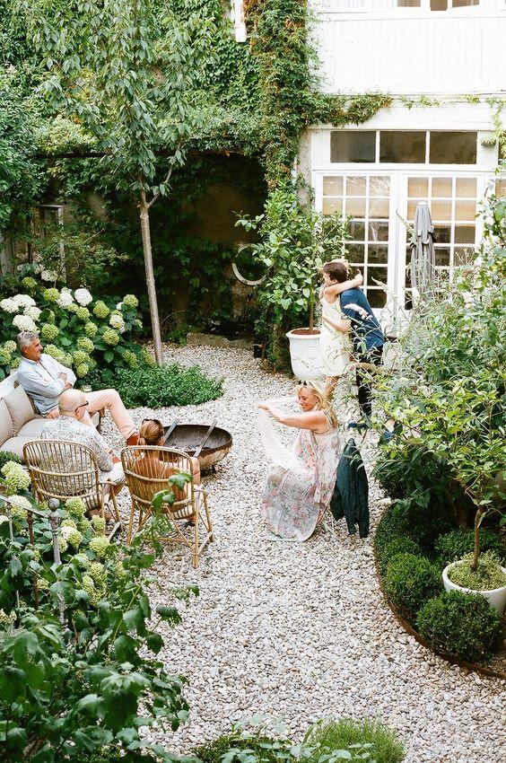 une petite cour arrière confortable avec du gravier au sol, des meubles en rotin et beaucoup de verdure et de fleurs blanches autour