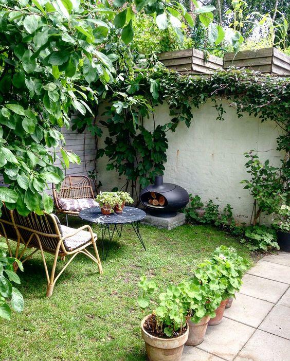 une petite cour arrière confortable avec des meubles en rotin, une table en marbre, un petit foyer et une pelouse verte