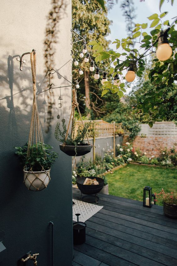 une petite cour nordique avec une terrasse noire, un foyer, des lanternes à bougie, une pelouse verte et beaucoup de fleurs