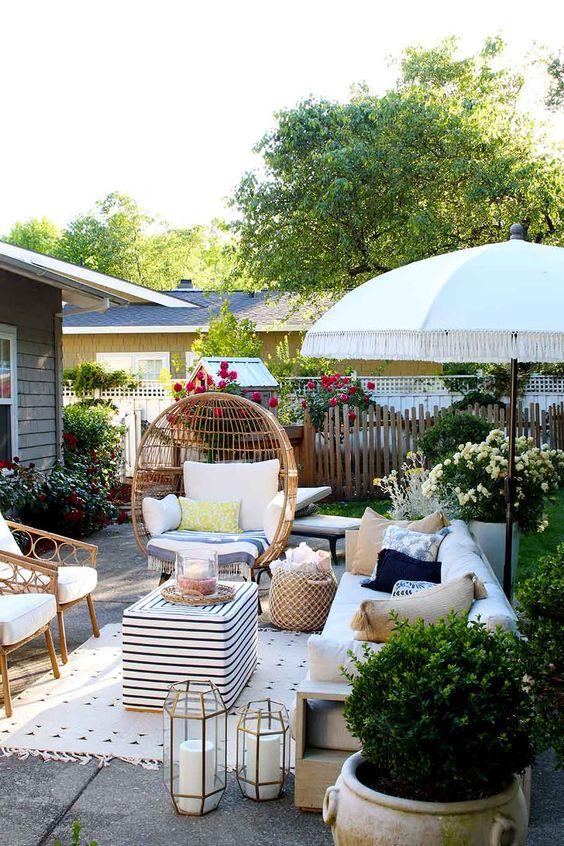 une cour d'été avec des meubles en rotin, des bougies, de la verdure en pot et des fleurs lumineuses tout autour