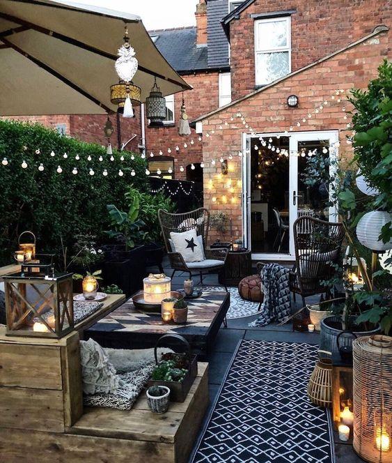un espace arrière petit mais élégant avec une terrasse en bois, beaucoup de verdure, des lumières, des bougies et des meubles en bois simples
