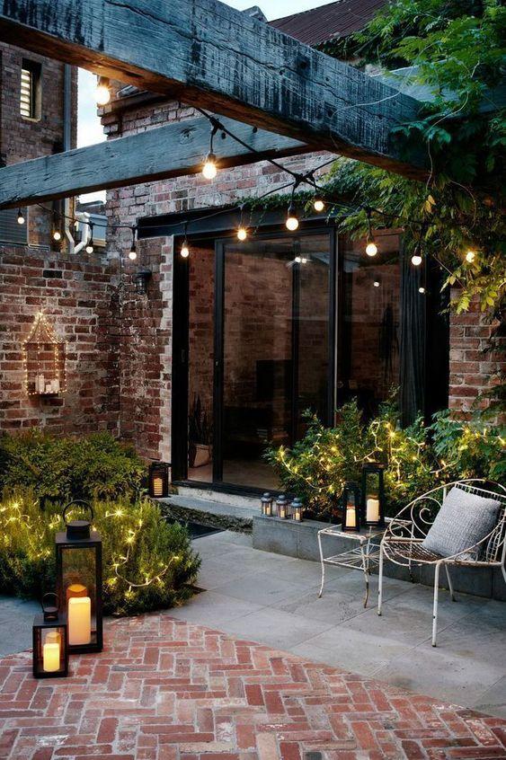 une petite cour chic revêtue de béton et de briques, avec de la verdure et des lumières et des lanternes à bougie semble invitante