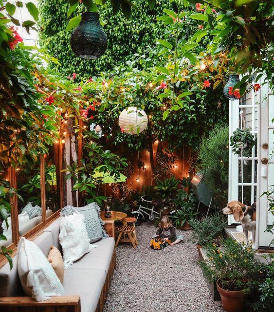 une petite cour très confortable avec beaucoup de verdure et de fleurs, des lumières, des lampes en papier et des meubles confortables