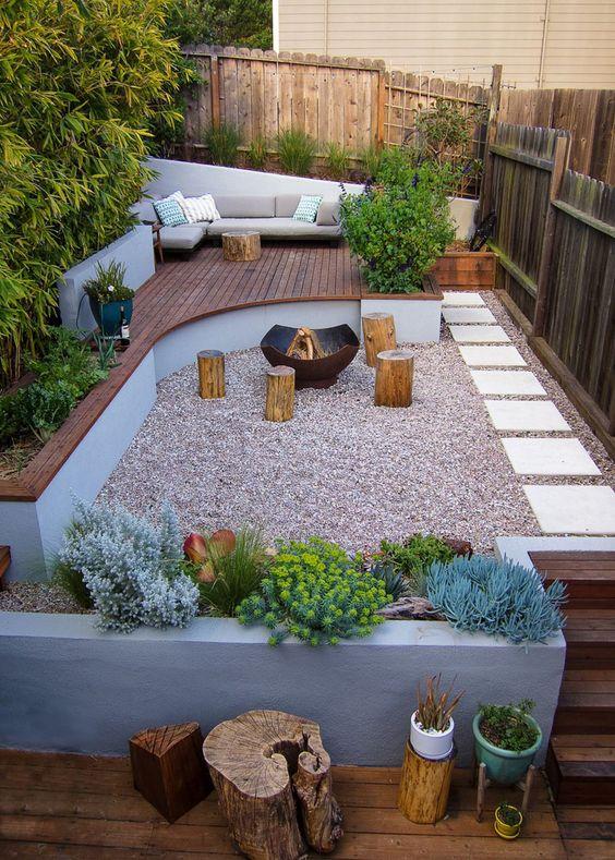 une cour arrière ultra-moderne avec une terrasse en bois avec des meubles, des jardinières en béton, des souches d'arbres et un foyer