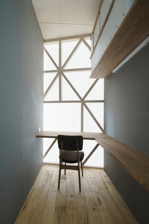 Le bureau à domicile est minuscule, il comprend un bureau flottant, des étagères ouvertes et de la lumière naturelle passant à travers le rideau