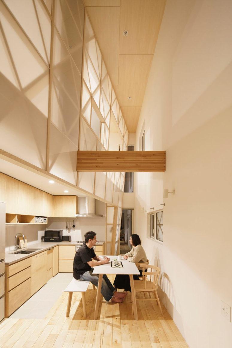 La cuisine est faite avec des armoires en contreplaqué élégantes, des lumières intégrées et des comptoirs en béton et un dosseret