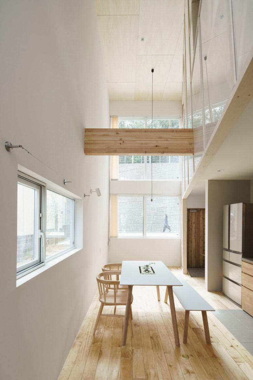 L'espace salle à manger est fait avec un ensemble de salle à manger simple avec un banc et des chaises et il y a une poutre en bois au-dessus de l'espace