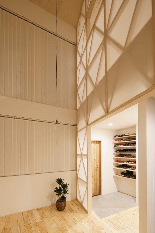 L'entrée est propre et minimale, avec des étagères ouvertes pour les chaussures et un tapis