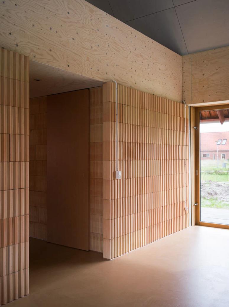 La terre cuite, le contreplaqué, le bois et le béton sont utilisés pour la décoration intérieure et extérieure de la maison et un tel combo semble inhabituel