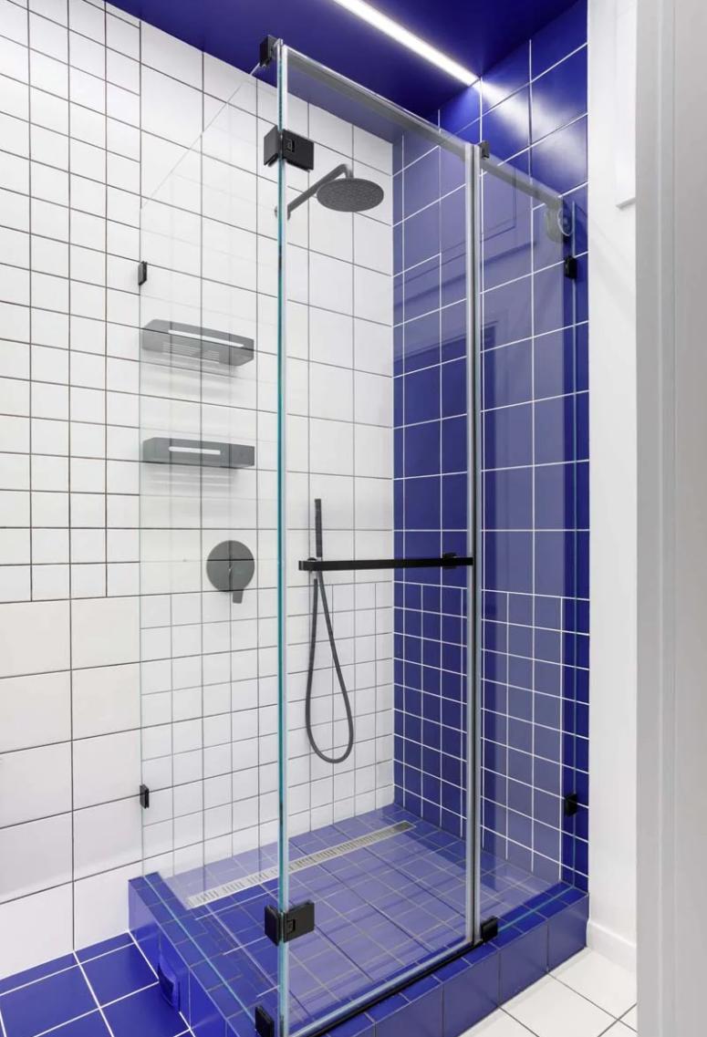 La salle de bain est faite de carreaux blancs, de coulis noir pour obtenir un look graphique et de carreaux bleus audacieux pour un accent