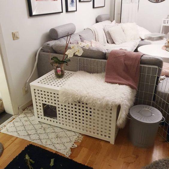 une table d'appoint blanche IKEA Hol avec un refuge pour animaux de compagnie à l'intérieur et une housse en fausse fourrure est un article à double fonction