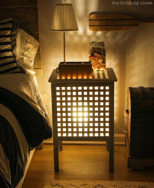 une petite table de chevet avec une lampe à l'intérieur est une veilleuse romantique qui créera une ambiance dans l'espace