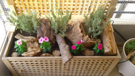 une table IKEA Hol placée sur un balcon pour la décoration et remplie de bois, de verdure et de fleurs pour un look naturel