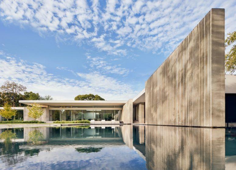 Il y a une grande piscine à côté de la maison, et elle adoucit l'aspect brutal des murs