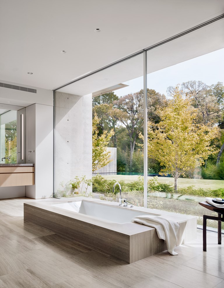 La salle de bain dispose d'une baignoire intégrée placée à côté d'un mur de verre pour profiter de la vue