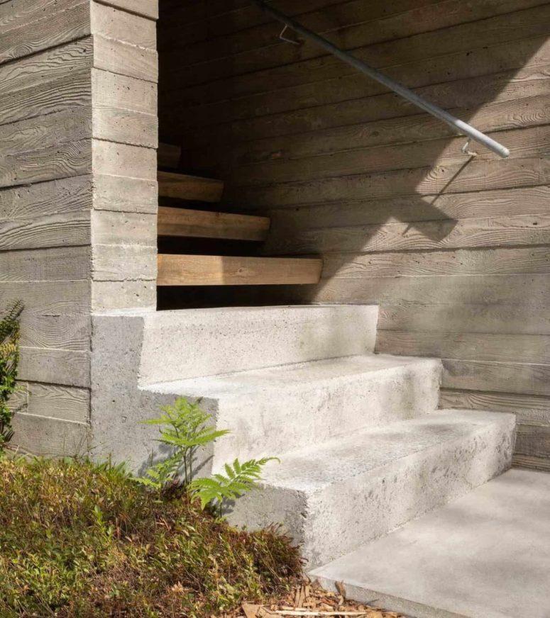 L'escalier d'entrée est construit en béton et en bois, avec une balustrade en métal pour une sensation moderne