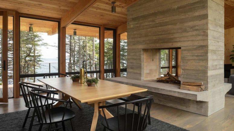 Il y a aussi un espace salle à manger plus formel avec des chaises noires et une cheminée double face qui divise les espaces