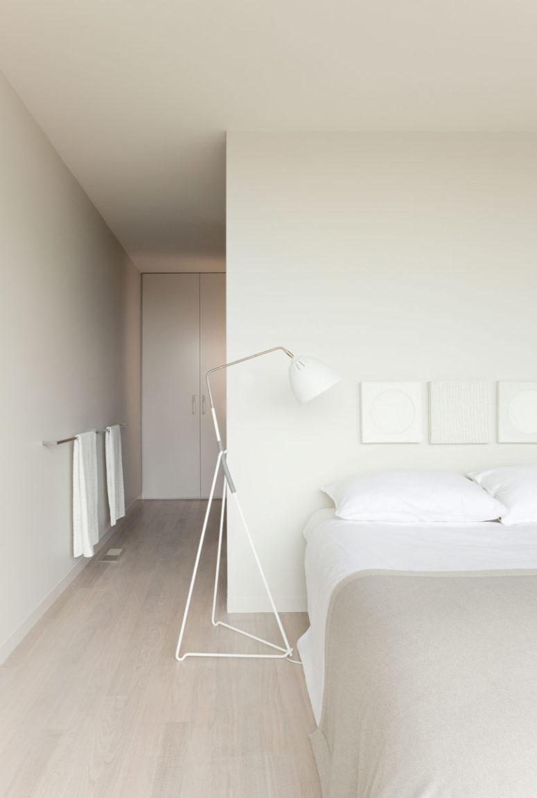 La chambre principale est entièrement neutre, avec des rangements fermés et cachés, un grand lit, des lampadaires et des textiles neutres