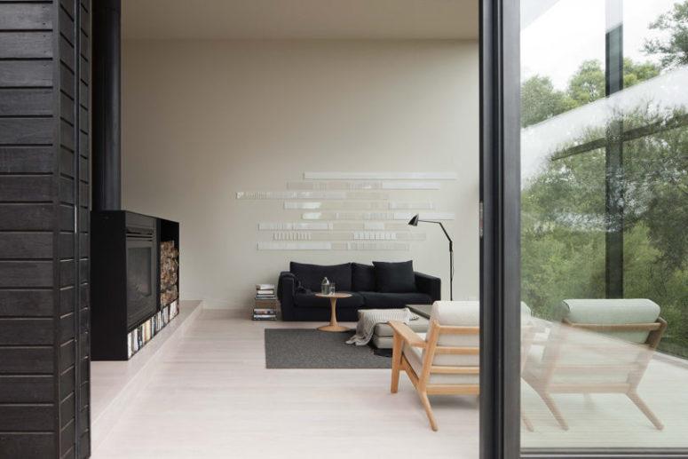 Le salon est fait avec un grand foyer, du bois de chauffage, un canapé noir et un art mural minimaliste cool