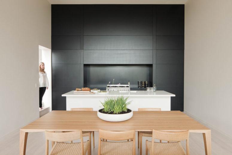 La cuisine est faite en noir, avec des armoires élégantes et tout est caché, l'îlot de cuisine est blanc et l'espace salle à manger est également ici