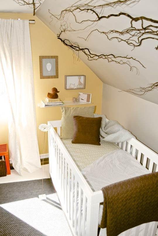 une pépinière mansardée lumineuse avec un mur d'accent jaune, des textiles confortables et un tapis plus un petit mur de galerie et des branches pour une touche naturelle