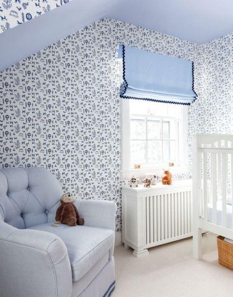 une pépinière de cottage bleu avec des murs de papier peint, des textiles et des tissus d'ameublement bleus ainsi que des meubles blancs