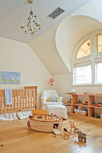une pépinière mansardée confortable et simple avec un plafond bleu, des meubles en bois, des jouets et un lustre vintage