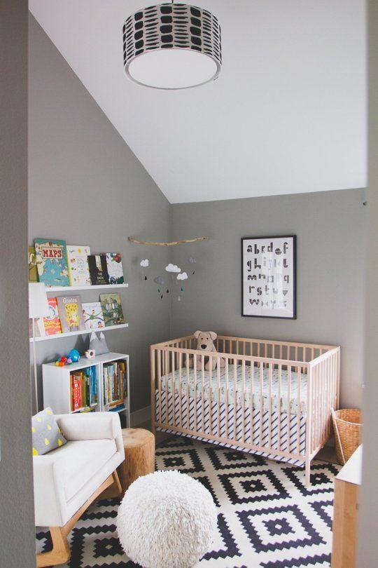 une chambre d'enfant décontractée avec des murs gris et un plafond blanc, un tapis imprimé, des meubles simples et une étagère pour lire à votre enfant